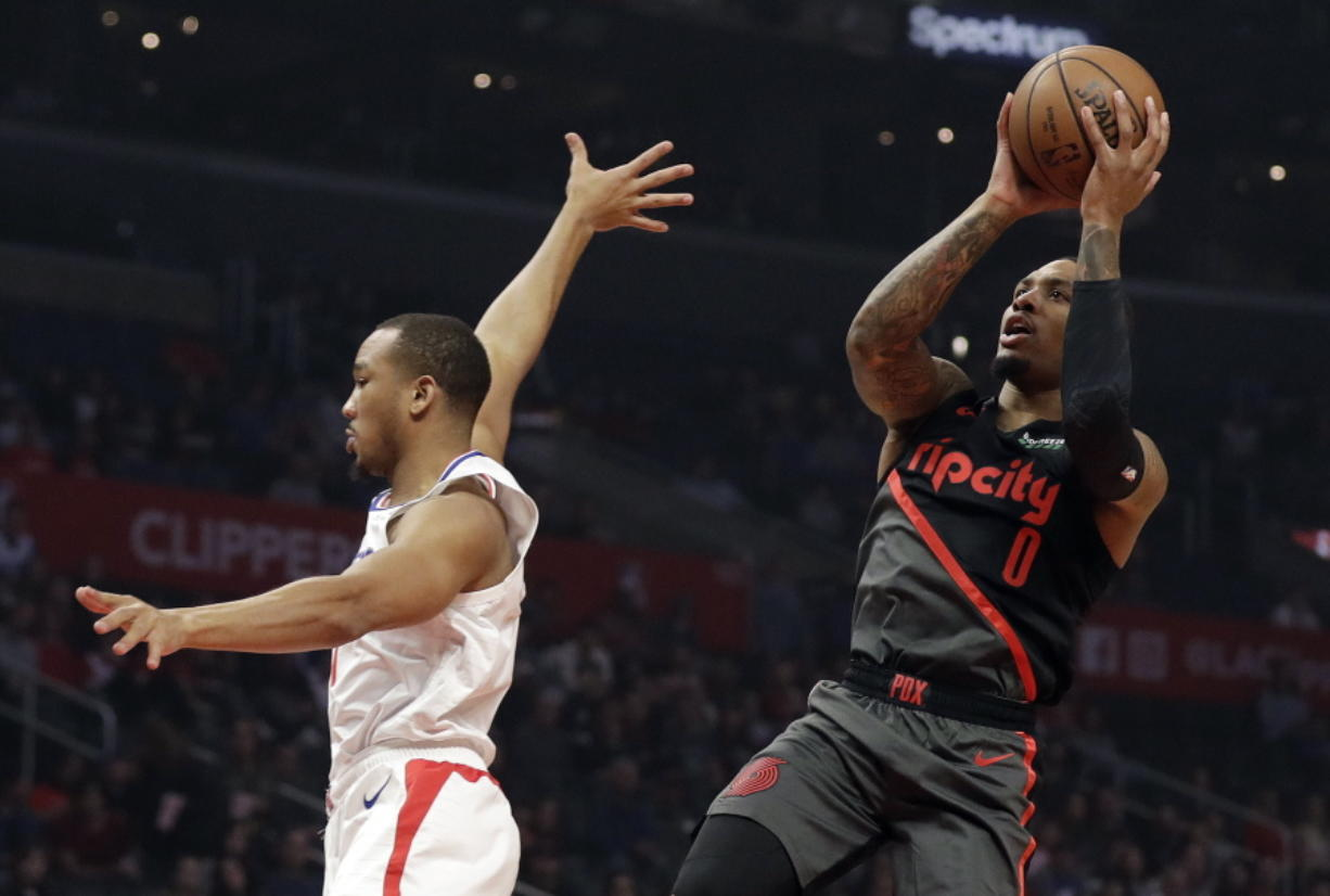Portland Trail Blazers' Damian Lillard (0) shoots over Los Angeles Clippers' Avery Bradley during the first half of an NBA basketball game Monday, Dec. 17, 2018, in Los Angeles.
