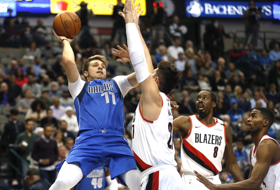 1314f4619444 Dallas Mavericks forward Luka Doncic (77) attempts a shot over Portland  Trail Blazers center