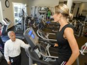 Nautilus CEO Bruce Cazenave, left, speaks with Amy Scharnhorst as she exercises on a StairMaster during her break at Nautilus' headquarters.