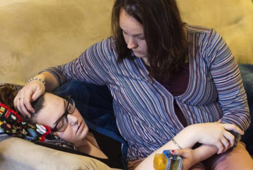 Miranda Neumann, right, embraces her 15-year-old daughter Elianna Neumann, left, recovering from her sixth round of viral meningitis, in January 2019. Miranda Neumann is holding baby food for her 6-month old.