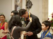 Union High School's Aaron Greene, 17, and the other performers at the Vancouver Symphony Orchestra's 25th annual Young Artists Competition get their medals Sunday at Trinity Lutheran Church after an afternoon of performing.