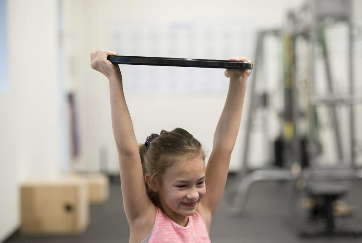 Richelle Endres, 10, of La Center shows her strength during a kids fitness class at Salmon Creek Bridge Chiropractic.