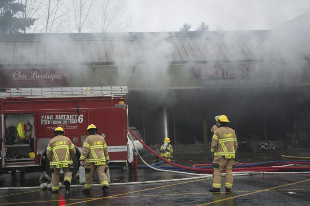 Firefighters from Fire District 6, Vancouver Fire Department and Clark County Fire and Rescue responded to the three-alarm fire Saturday at Holly Park Shopping Center in Hazel Dell.
