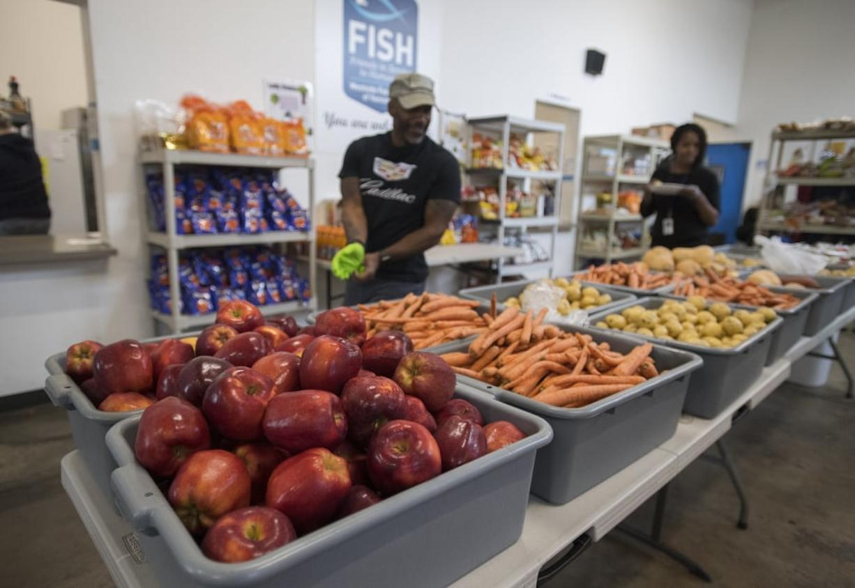 Volunteer Eddie Odoms, with hat, looks over the fresh fruit and vegetables available for those in need at FISH Westside Food Pantry of Vancouver on Monday morning.