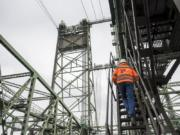 Interstate 5 Bridge Supervisor Marc Gross, with the Oregon Department of Transportation, climbs a ladder leading to the bridge's machine room during a tour on Thursday morning.