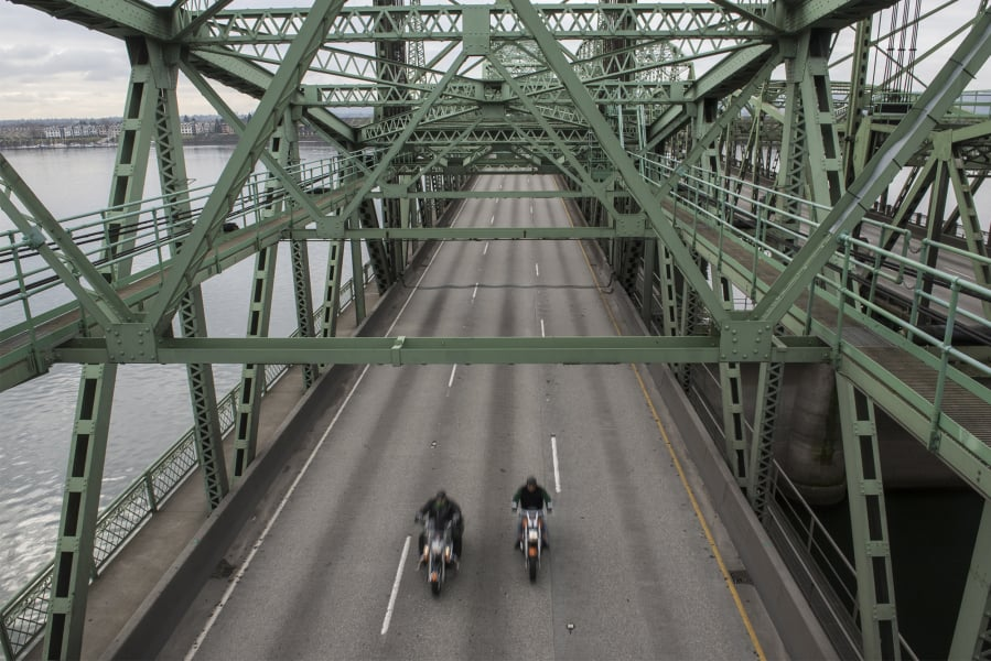 Two motorcycles drive North along the Interstate 5 Bridge.