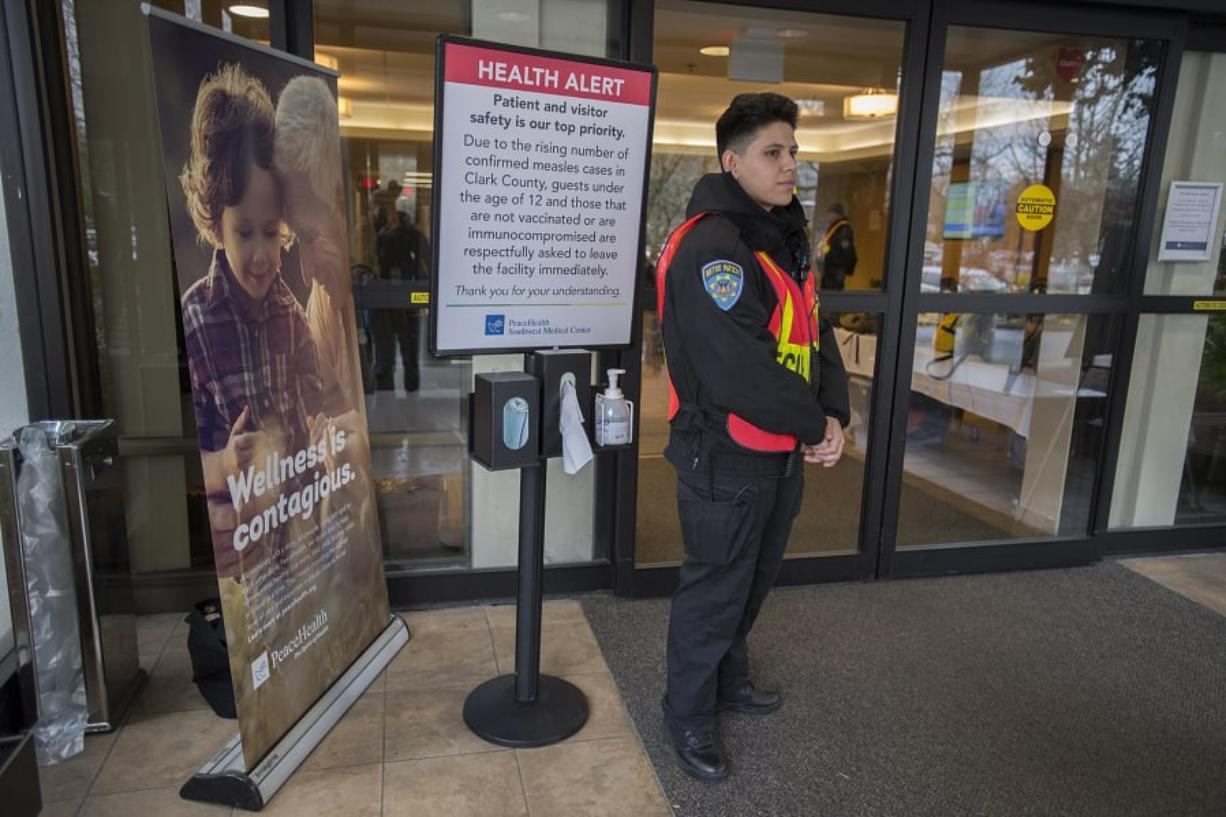 A hospital security worker, who declined to be identified, stands at a door at PeaceHealth Southwest Medical Center in Vancouver while screening for visitors under 12 years old and those who have not been vaccinated for measles as part of the hospital's measles outbreak protocol. Children, especially kids under 5, are especially vulnerable to contracting measles. Amanda Cowan/The Columbian