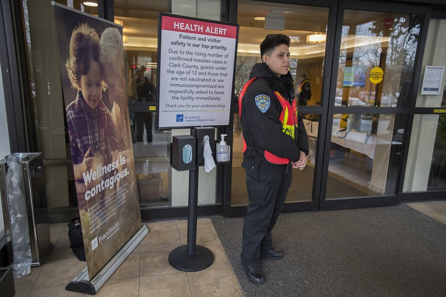 A hospital security worker who declined to be identified stands at a door at Peace Health Southwest