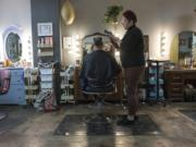 One of the perks of being an independent hairstylist is getting to pick your clients. Shelby Oxley cuts the hair of her husband, Barry Oxley, at the station she rents in Marquee Salon + Studio.