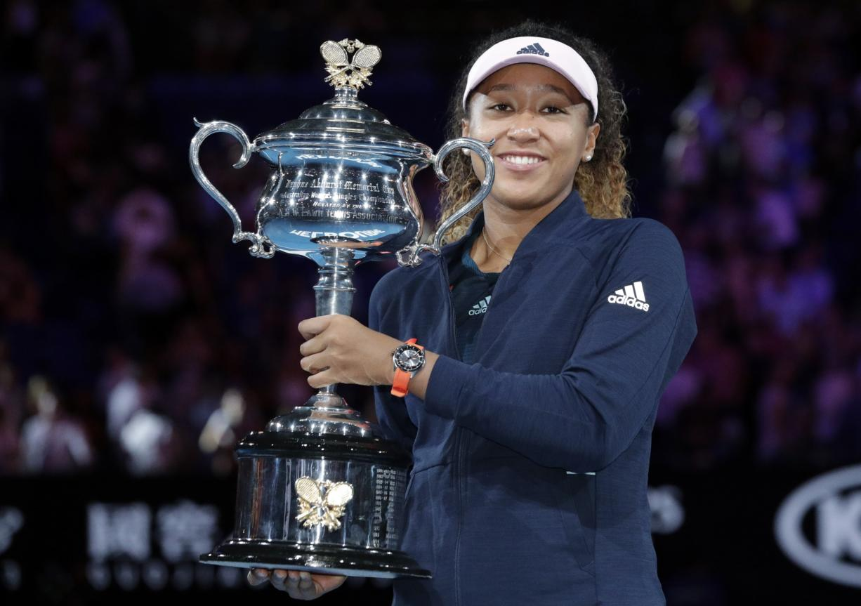 Japan's Naomi Osaka poses with her trophy after defeating Petra Kvitova of the Czech Republic in the women's singles final at the Australian Open tennis championships in Melbourne, Australia, Saturday, Jan. 26, 2019.