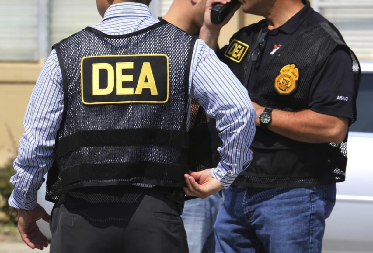 FILE - In this June 13, 2016, file photo, Drug Enforcement Administration (DEA) agents arrive on the scene of a fatal shooting in Florida. U.S. federal narcotics agent, Jose Irizarry, is accused of conspiring with a longtime DEA informant to launder more than $7 million in illicit drug proceeds from the U.S. to traffickers in Colombia, according to several current and former law enforcement officials.