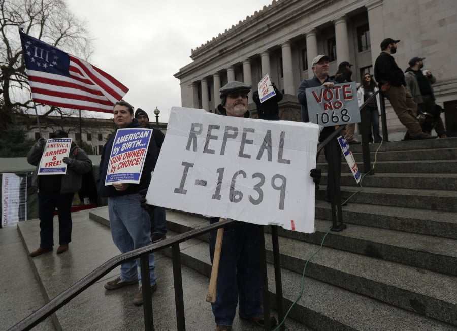 "Rick Howell, of Wenatchee, Wash., holds a sign that reads ""Repeal I-1639"" as he takes part in a gun-rights rally, Friday, Jan. 18, 2019, at the Capitol in Olympia, Wash. Initiative 1639, which was passed by voters in November, 2018, is a package of gun regulations that includes raising the legal age to buy any semi-automatic rifle to 21. (AP Photo/Ted S."