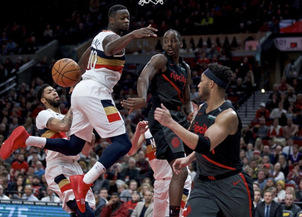 Portland Trail Blazers forward Al-Farouq Aminu, center, passes around New Orleans Pelicans forward Julius Randle during the second half of an NBA basketball game in Portland, Ore., Friday, Jan. 18, 2019. The Trail Blazers won 128-112.