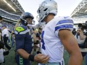 Seattle Seahawks quarterback Russell Wilson, left, greets Dallas Cowboys quarterback Dak Prescott, right, following their game on Sept. 23, 2018 in Seattle.