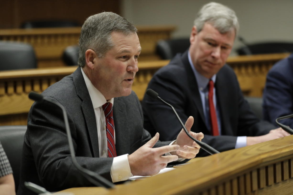 House Minority Leader J.T. Wilcox, R-Yelm, left, speaks as House Majority Leader Pat Sullivan, D-Covington, looks on Thursday during the Leadership Panel of the Associated Press Legislative Preview at the Capitol in Olympia.