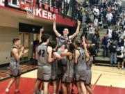 The Union boys basketball team lifts up Ethan Smith moments after an 82-68 win over Camas in which he hit a school-record eight 3-pointers on Friday night at Camas High School.