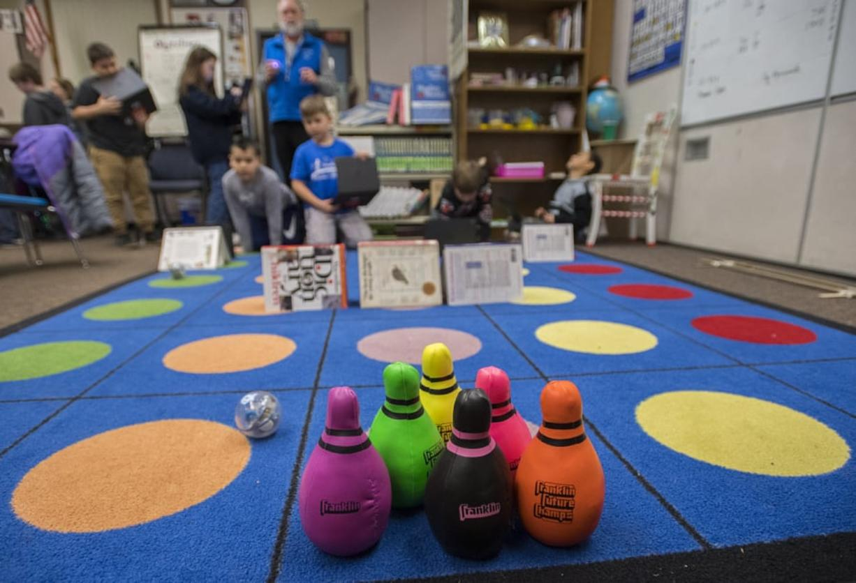 "Teacher Mark Sterling, blue vest, and a fourth-grader at Silver Star Elementary School watch as they maneuver a ""sphero"", left, in an attempt to knock down stuffed bowling pins while controlling them from across the room. A program levy and technology levy were both passing Tuesday night."