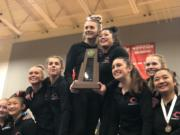 Camas gymnastics team members hoist the state championship trophy on the podium at state.