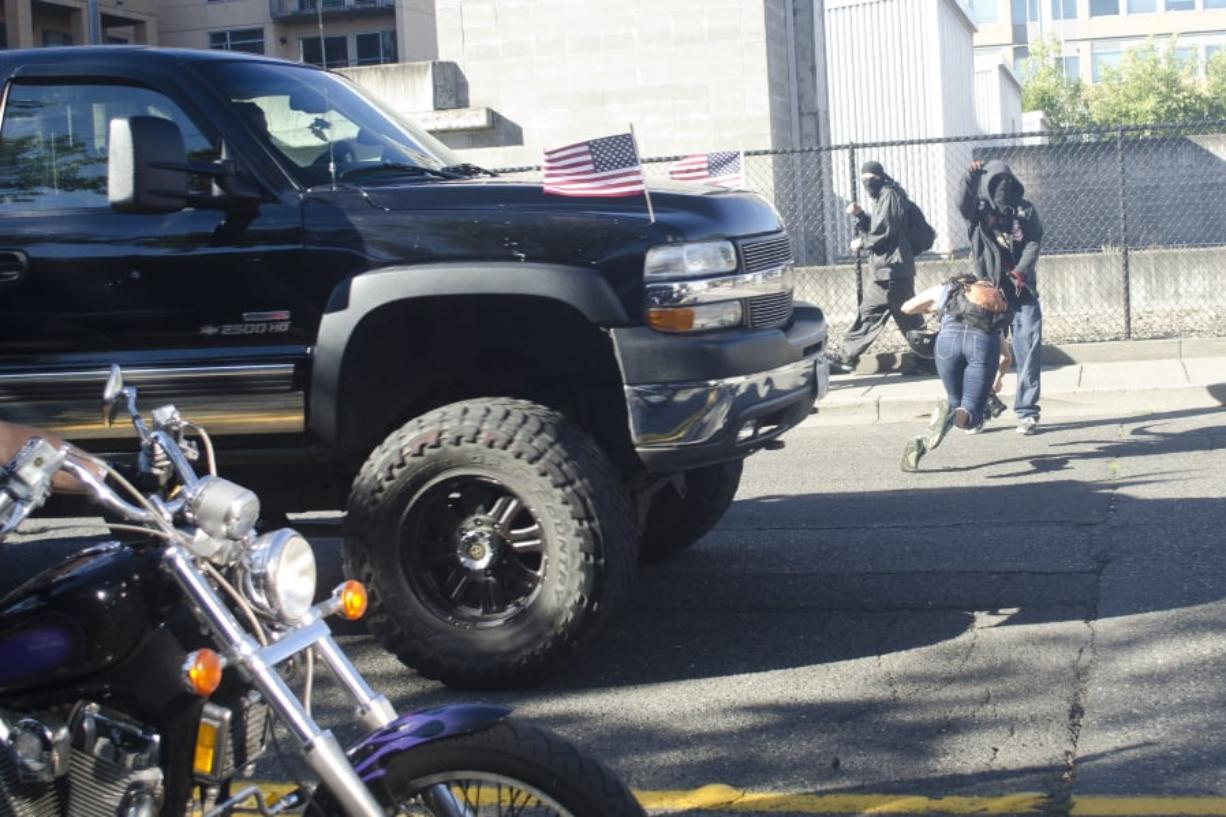 A photographer dives out of the way of a speeding truck after a rally held by Joey Gibson's Patriot Prayer group in Vancouver on Sept. 10, 2017. The event had been moved to Vancouver from Portland in an attempt to avoid protesters. (The Columbian files)