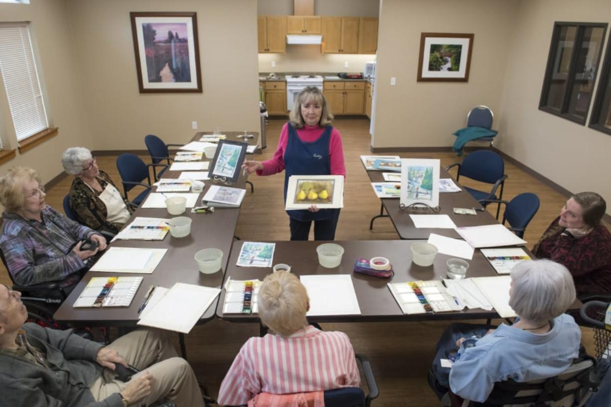 Nathan Howard/The Columbian Becky Leventis shows a painting to seniors at The Quarry Senior Living. Leventis teaches monthly art classes at The Quarry, its sister facility Glenwood Place Senior Living, and less often at Prestige Senior Living Bridgewood.