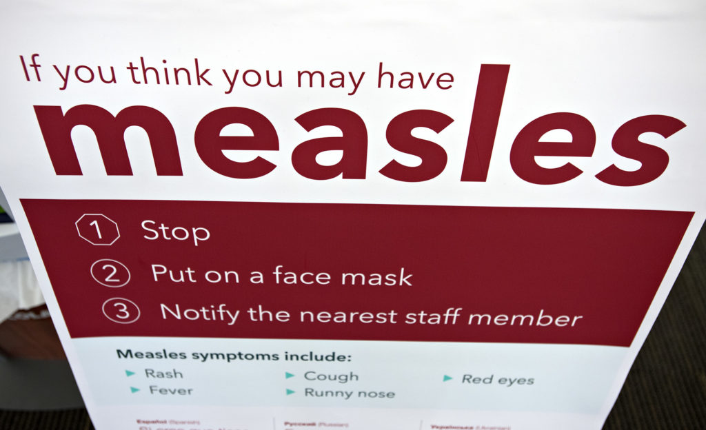 An informational sign about the measles is posted in the entrance of the Kaiser Permanente Cascade P