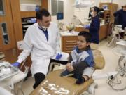 Dr. Joseph Kelly, left, chats with 9 year-old Samuel Pena, right, at a free children's dental clinic held Saturday at Clark College.