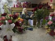 Florist Jane BonVillain arranges a vase of red roses at Ridgefield Floral & Gifts. Though Ridgefield is her hometown, she began her floral career working in a shop in Manhattan and returned to Clark County to be closer to her mother.