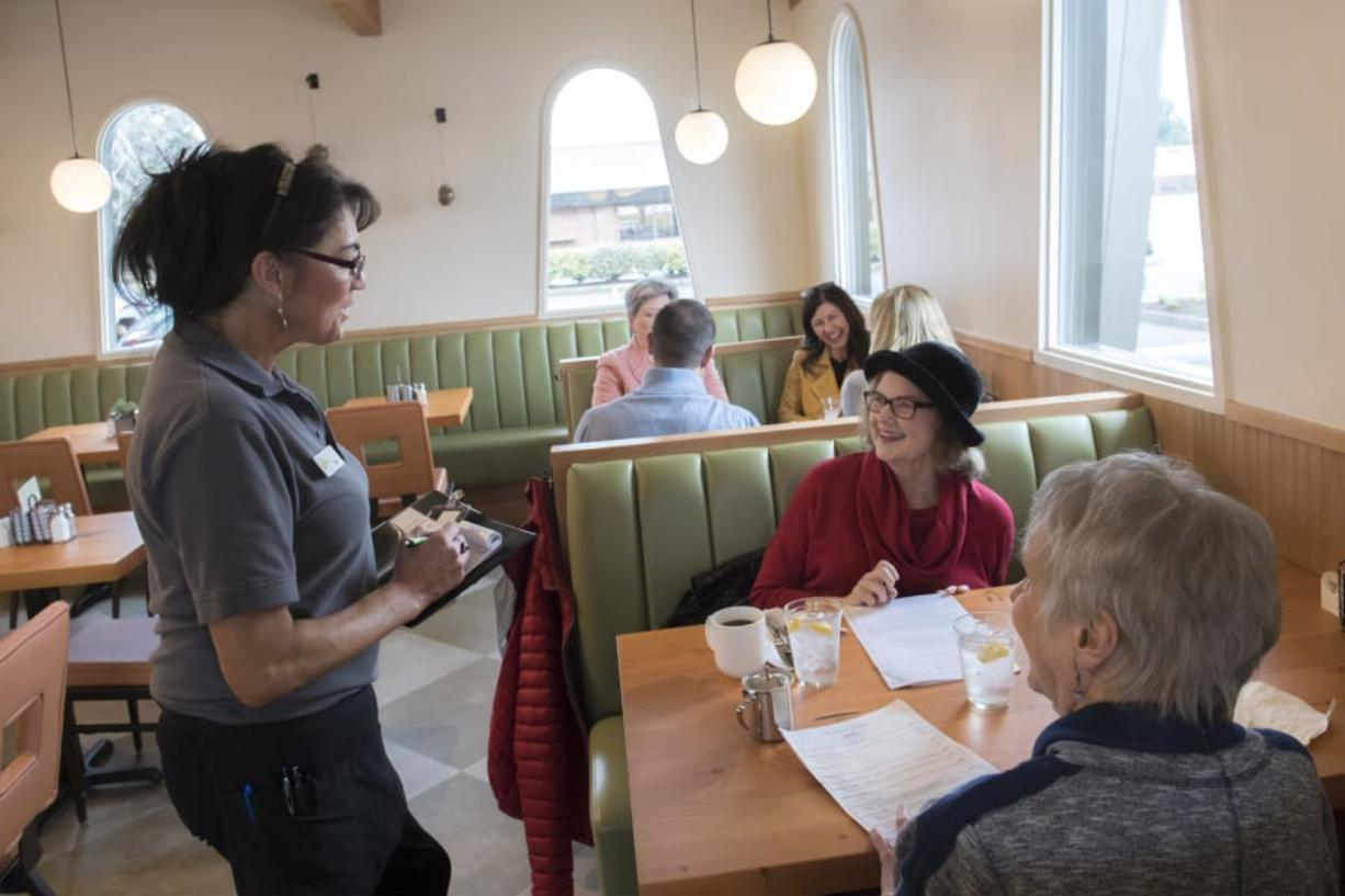 """Dea Taylor, from left, takes a lunch order from Carolyn Walz and Anne Garlinghouse during the lunch rush Tuesday at The Diner Vancouver, a new restaurant owned by Meals on Wheels People that had a soft opening Feb. 11. """"We have so many repeat customers already,"""" Taylor said. (Nathan Howard/The Columbian)"""