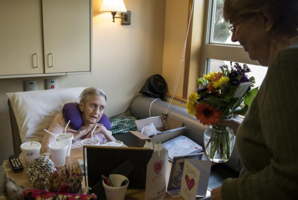 "Ray Hickey Hospice House resident Mary Lou Jensen, left, thanks PeaceHealth hospice volunteer Kathi Anderson of Vancouver as Anderson delivers her flowers from the Portland-based The Bloom Project at the hospice home in Vancouver. ""In a place where people are sad or not doing well, it's a bright spot,"" Anderson said."