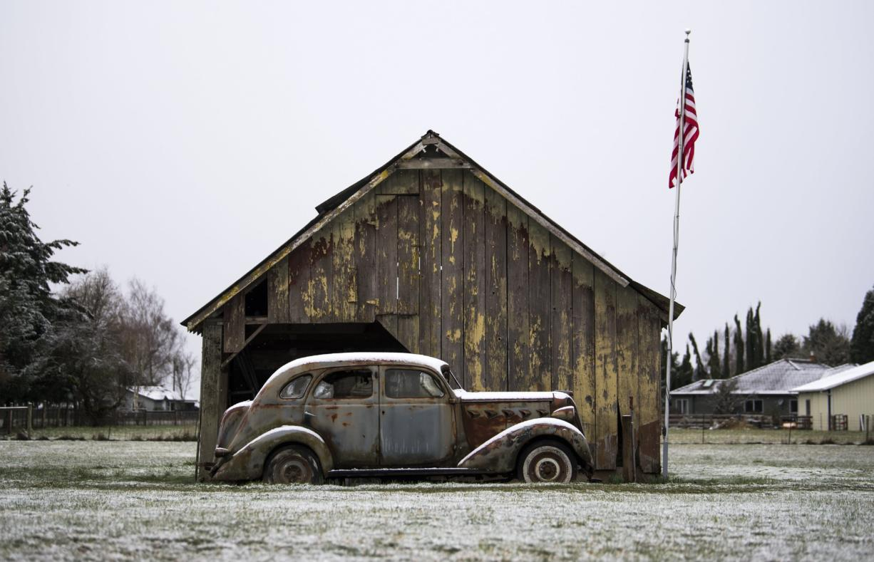 A dusting of snow rests on an old barn and car along NW 41st Avenue in Vancouver on Feb. 25, 2019. (Alisha Jucevic/The Columbian files)
