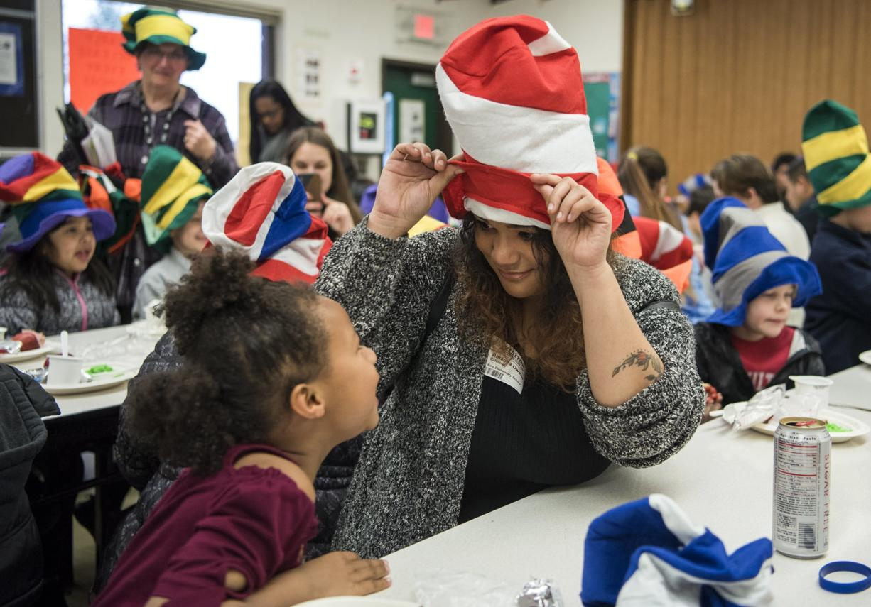 Martin Luther King Elementary School first-grader Nyah Owens, left, and her mother, Amanda Owens, goof around with their Dr. Seuss hat at the elementary school in Vancouver on Wednesday morning.
