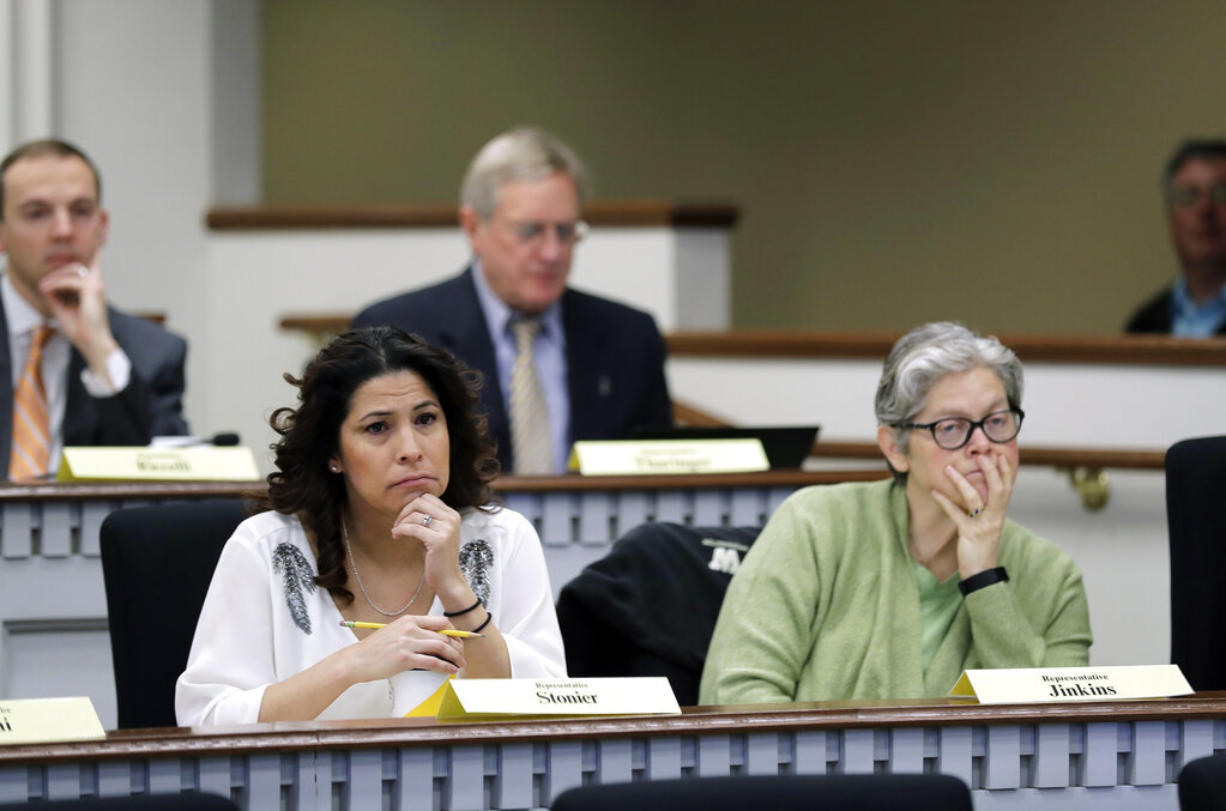 Rep. Monica Stonier, D-Vancouver, lower left, and Rep. Laurie Jenkins, D-Tacoma, right, listen Friday, Feb. 8, 2019, during a public hearing before the House Health Care & Wellness Committee at the Capitol in Olympia, Wash. Amid a measles outbreak that has sickened people in Washington state and Oregon, lawmakers heard public testimony Friday on a bill that would remove parents' ability to claim a philosophical exemption to opt their school-age children out of the combined measles, mumps and rubella vaccine. (AP Photo/Ted S.