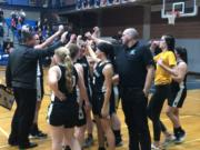 The Woodland girls basketball team cheers after a 64-43 2A district win over Ridgefield at Hockinson High School on Thursday.