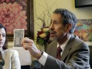Dr. Gary Goldbaum of the Washington State Medical Association holds up a picture of his brother as a child, when he was in a wheelchair due to polio, at Wednesday's hearing on a vaccination bill.