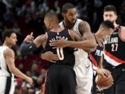 Portland Trail Blazers guard Damian Lillard, front, greets a former teammate, San Antonio Spurs center LaMarcus Aldridge, before an NBA basketball game in Portland, Ore., Thursday, Feb. 7, 2019.