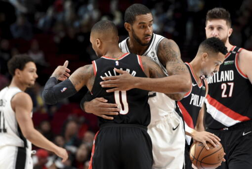 Portland Trail Blazers guard Damian Lillard, front, greets a former teammate, San Antonio Spurs center LaMarcus Aldridge, before an NBA basketball game in Portland, Ore., Thursday, Feb. 7, 2019.