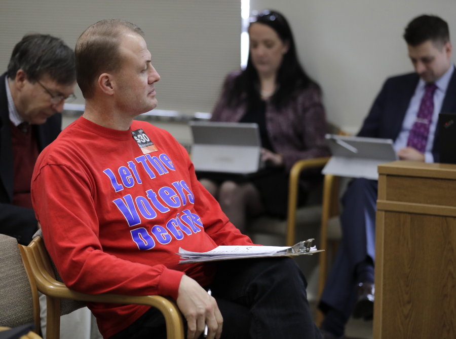 "Anti-tax initiative promoter Tim Eyman, center, waits before speaking during a Feb. 13 public hearing of the Senate State Government, Tribal Relations, and Elections Committee at the Capitol in Olympia. Eyman testified Tuesday in favor of his ""Bring Back Our $30 Car Tabs"" initiative."