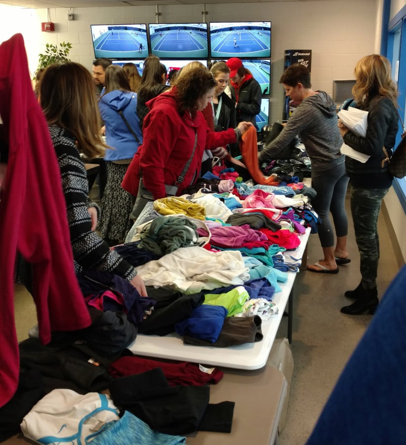 Players and parents search over tennis clothing during the Vancouver Tennis Center Foundation gear swap on Sunday, March 3, 2019. The 2020 gear swap is Sunday, March 8.