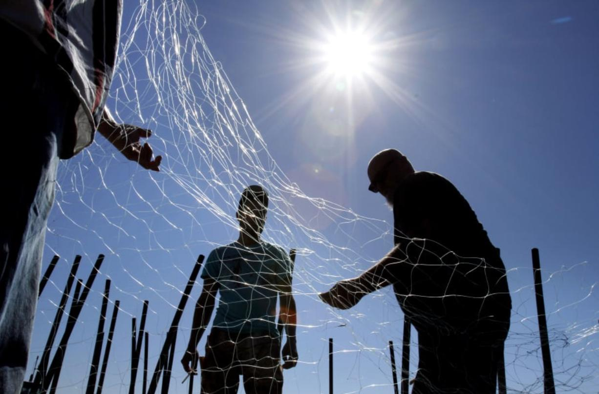 Gillnetters repair a net in Astoria, Ore. A controversy has erupted over changes to the Columbia River Reforms passed by the Washington Fish and Wildlife Commission in Spokane, WA. The changes will allow for more gillnetting in the lower Columbia. Files/The Columbian