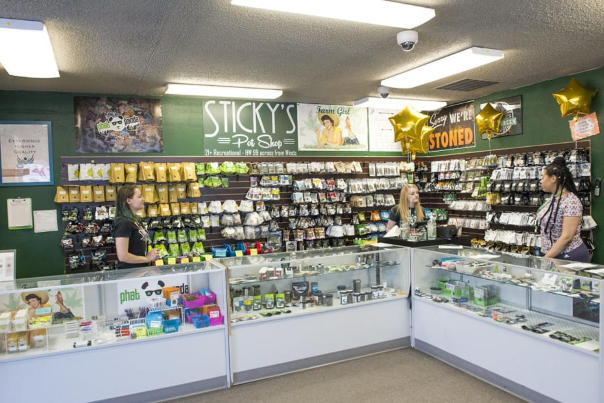 Budtenders at Sticky's Pot Shop wait for customers to arrive for a closing sale in July following a court decision that led to the store's closing. Nathan Howard/Columbian files