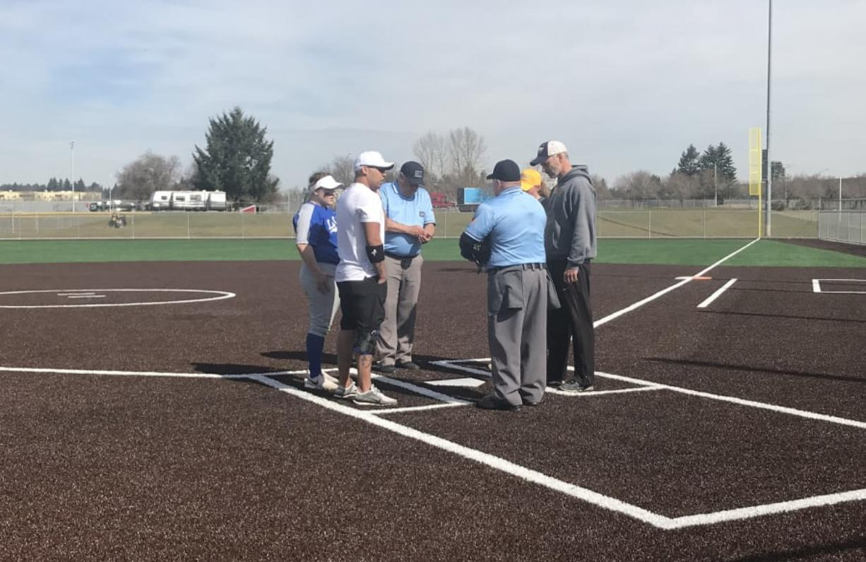Coaches from La Center and Hudson's Bay meet with umpires before the second game of Saturday's Trapper Softball Classic.