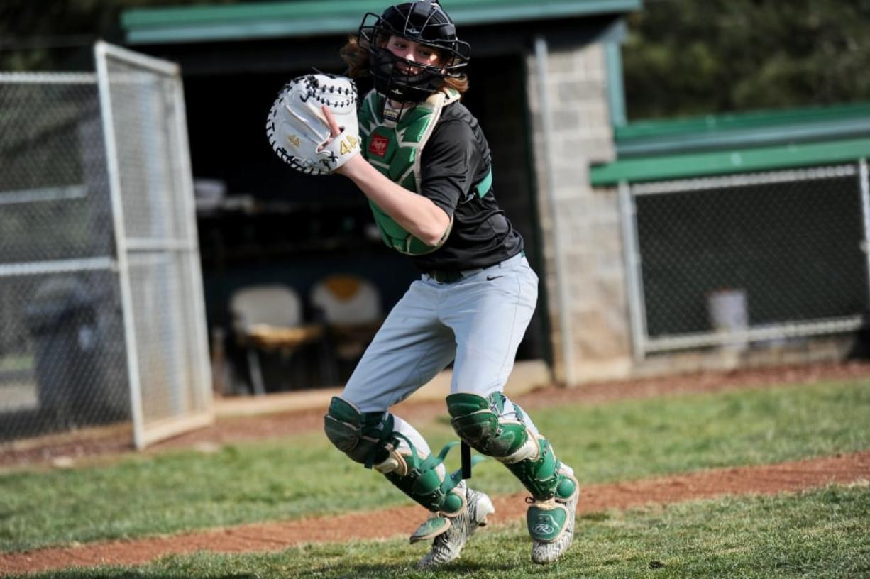 Evergreen senior catcher Blake Whitehead, the glue guy on a small roster, winds up to throw a ball to coach Chad Burchett at Evergreen High School. Andy Buhler/The Columbian
