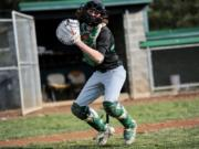 Evergreen senior catcher Blake Whitehead, the glue guy on a small roster, winds up to throw a ball to coach Chad Burchett at Evergreen High School.
