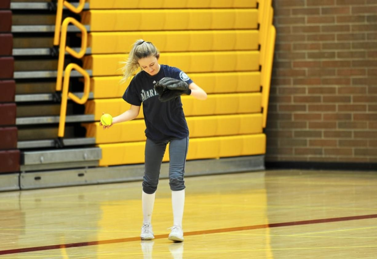 Prairie center fielder Ashley Shelton gathers herself after catching a pop fly during an indoor practice in Prairie High School's gym. (Andy Buhler/ The Columbian)