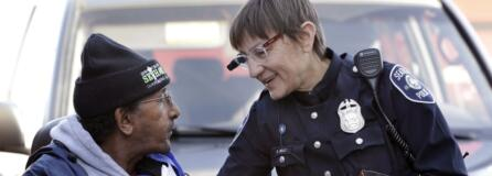 Seattle police Officer Debra Pelich, right, wears a video camera on her eyeglasses as she talks with Alex Legesse before a small community gathering in Seattle in 2015. While the Seattle Police Department bars officers from using real-time facial recognition in body camera video, privacy activists are concerned that a proliferation of the technology could turn the cameras into tools of mass surveillance. The ACLU and other organizations in May 2018 asked Amazon to stop selling its facial-recognition tool, called Rekognition, to law enforcement agencies.