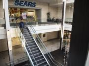 A shopper walks down the stairs near the former Sears location at the Vancouver Mall in November. The space will apparently be split into a Hobby Lobby and a Round1 amusement center.