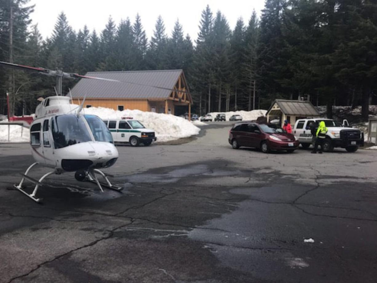 A helicopter and search-and-rescue personnel are seen at Marble Mountain Sno-Park as part of a rescue effort for two men who were stuck on Mount St. Helens overnight Sunday.