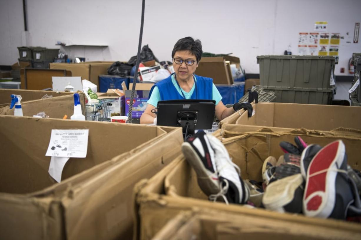 Lucia Mercado of Washougal sorts items in the intake area of Goodwill in Vancouver on Feb. 1.