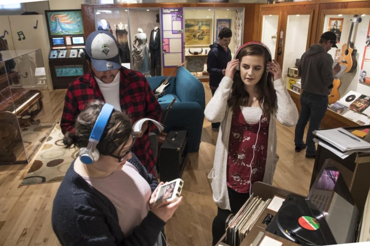 """Washington State University Vancouver history students Ruby Burke, left, Brian Sanchez and Katie O'Boyle sample the sound technologies of yesteryear while studying """"Music, Movement and Sound,"""" an interactive exhibit that opened in January at the Clark County Historical Museum."""