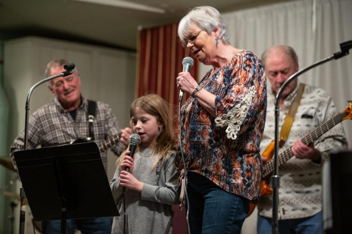 "Six-year-old Megan Wilder helps her grandmother, Eilene Laing, sing ""You Are My Sunshine"" during the biweekly gathering of the Columbia River Old Time Strings at the Minnehaha Grange. Accompanying them are Jerry Jacobs on guitar and Ron Coon on bass. Randy L. Rasmussen for The Columbian"